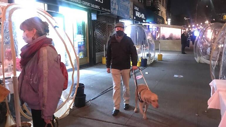 Peter Slatin and his guide dog on the sidewalk in New York City