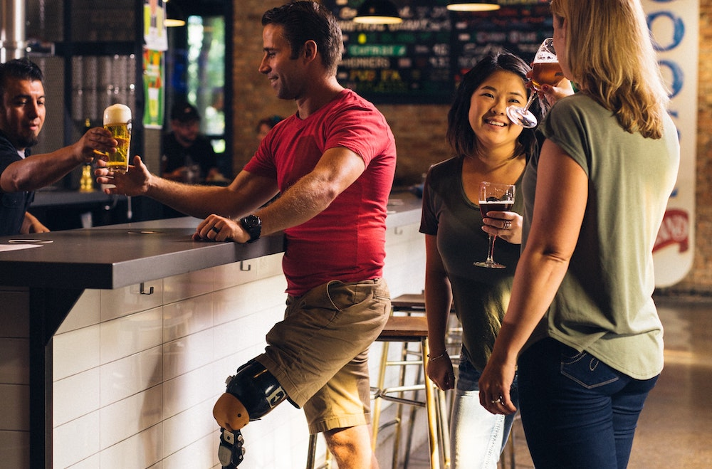 Man with prosthetic leg standing at bar