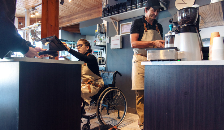 Woman in wheelchair works enters order into POS system in coffee shop